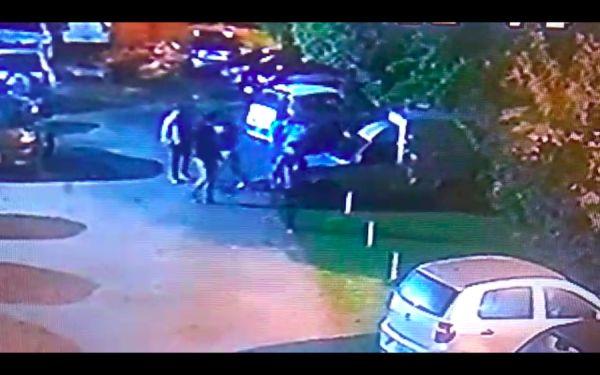 Ya el joven yace inconsciente detrás de un vehículo.